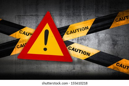 Warning sign with exclamation mark on striped caution tape