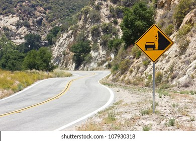 Warning sign for falling rocks on a curvy road.