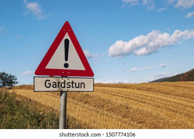 Warning sign for a farmyard in Norway  (gårdstun = farmyard), signpost in the countryside background, blue sky, clouds and stubble field.
