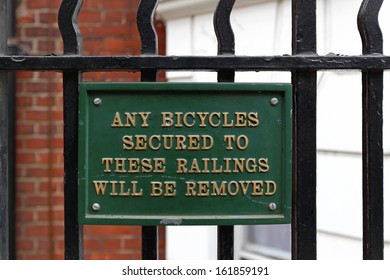 Warning sign forbiding bicycles left secured on fence