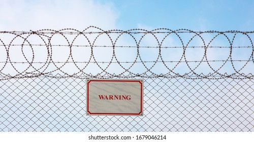 Warning sign hangs on a metal barbed wire fence ensuring safety and security.