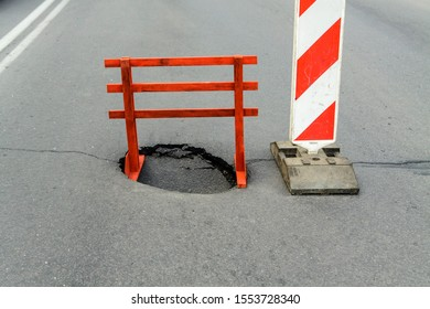 Warning sign and a hole on the road. Dangerous place.