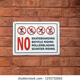 Warning Sign: No Skateboarding, bicycle riding, rollerblading, scooter riding on a brick wall