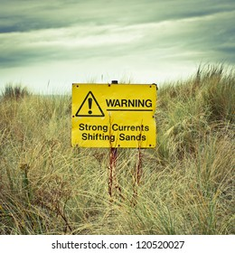 Warning sign on a british beach on a stormy day