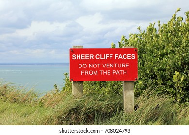 Warning Sign On Coastal Path. Sheer Cliff Faces Do Not Venture From The Path.