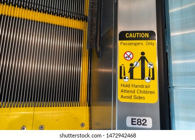 A warning sign on an escalator that says to take caution while riding.