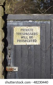 Warning sign on a gate saying private, trespassers will be prosecuted