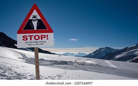A warning sign on the vast Jungfrau Glacier, high in the Swiss Alps above Interlaken, Switzerland.