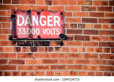 """Warning sign outside an electricity substation saying """"Danger, 33,000 volts"""""""