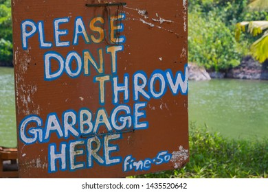 """Warning sign """"Please dont throw garbage fine-50"""" on green natural background. Ecology concept."""