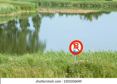 Warning sign prohibiting swimming over lake background.