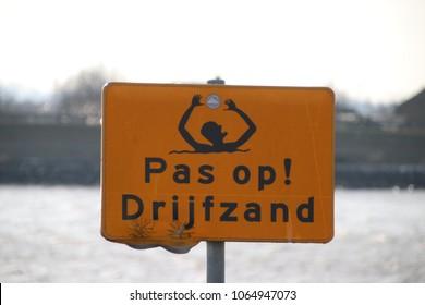 warning sign for quicksand at the Hollandse IJssel riverside.