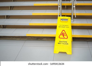 Warning sign with Russian text caution wet floor. A sign near the steps in an office or entertainment center. Cleaning ceramic tiles in a store. Copy space