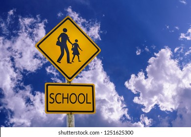 Warning sign, school sign for students school crossing the street with blue sky.
