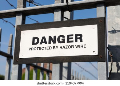 A warning sign stating Danger Protected by Razor Wire mounted on railings outside a business in Warrington May 2018