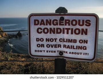 Warning sign at a steep cliff on the Palos Verdes Peninsula near Los Angeles on the edge of the Pacific Ocean with a slightly humorous tone.