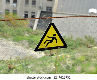 """Warning sign """"Steep slope. Danger of falling"""" is attached to a metal fence around a steep dangerous slope of a mountain"""