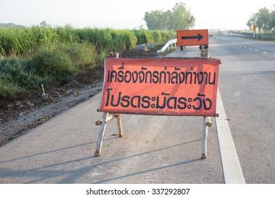 warning sign in Thai language translate in English is beware running machine