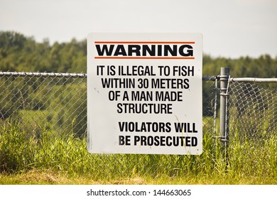 A warning sign that it's illegal to fish close to a man made structure