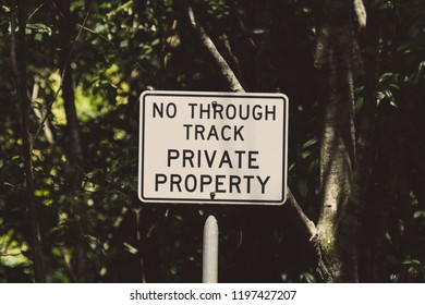 "A warning sign that reads ""No Through Track - Private Property"""