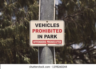 "A warning sign that reads ""Vehicles Prohibited In Park - Offenders Prosecuted"""
