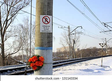 "Warning sign ""To walk on railroad tracks is forbidden!"" and funeral wreath"