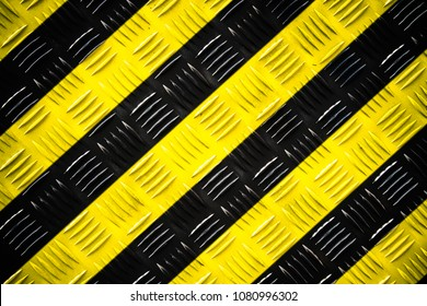 Warning sign yellow and black stripes painted over steel checker plate (or diamond plate) on the floor as texture background. Concept for do not enter the area, caution, danger, hazard.