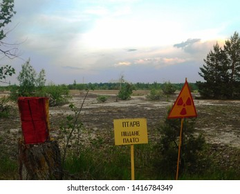"Warning signs with the Chernobyl NPP sarcophagus on the horizon. Translation: ""Point of Temporary Localization of Radioactive Waste (PTLRW) Sandy Plateau."""