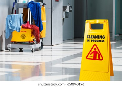 The warning signs cleaning in process the floor of the building and janitorial car parked in back to prevent corona virus covid-19 infection.