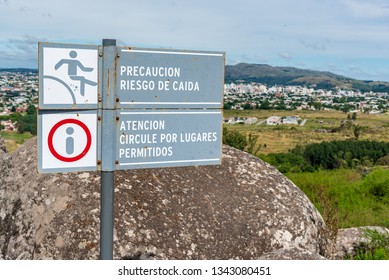 """Warning signs of fall in spanish meaning """"Precaution risk of falling"""" and """"Attention circulate through allowed places"""", with a landscape of a city in the back"""