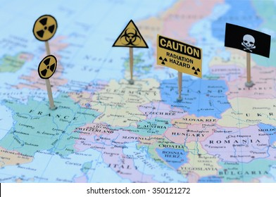 Warning signs including a skull, biohazard warning, nuclear warning and radiation hazard on a map of Europe - illustration image. Selective focus (nuclear hazard is focused, the others are unfocused)