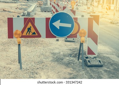 Warning signs for work in progress on road under construction. Vintage and retro style and shallow dof.