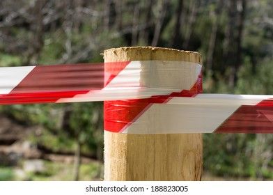 Warning tape attached to a wooden pole and used as a parapet