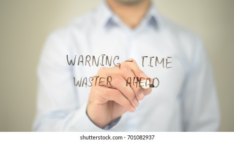 Warning - Time waster Ahead, man writing on transparent screen