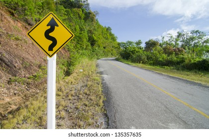 warning winding traffic sign winding road on background
