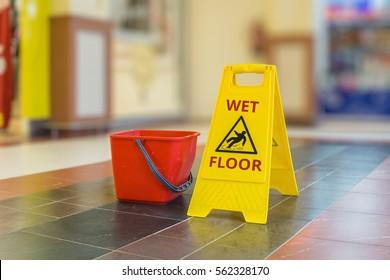 Warning yellow plastic sign of wet floor.