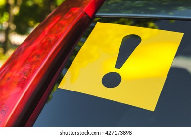 Warning yellow sticker with black exclamation sign over rear window of modern car, novice driver