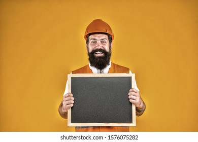 Warranty service. Handsome repairman. Man bearded repairman builder work clothes. Responsibility and garanties. Engineering and architect occupation. Repairman engineer hold blackboard copy space.