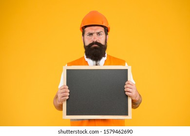 Warranty service. Responsibility and garanties. Engineering and architect occupation. Repairman engineer hold blackboard copy space. Handsome repairman. Man bearded repairman builder work clothes.