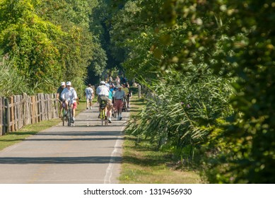 Warren, Rhode Island, USA - August 4, 2007: Cluster of cyclists and walkers enjoying the shimmering summertime heat along the East Bay Bike Path