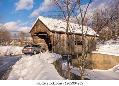 WARREN, VERMONT, USA - JANUARY 1, 2013: Car enters covered bridge over Mad River.