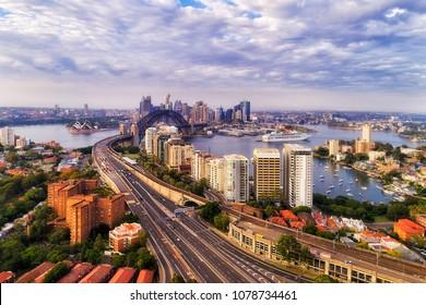Warringah freeway with Sydney trains railway towards Sydney Harbour bridge and city CBD landmarks around Sydney harbour in elevated aerial view.