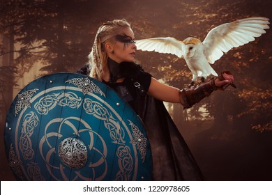Warrior, beautiful white owl, Viking blonde woman with shield and sword, braids in her hair.