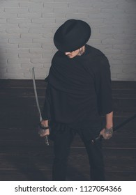 Warrior in black hat and clothes, top view. Man with swords standing on wooden floor. Samurai, buddhist concept. Honor and dignity. Harakiri, suicide ritual.