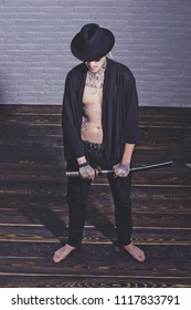 Warrior in black hat and open clothes showing tattooed torso. Man with sword standing on wooden floor barefoot, top view. Honor and dignity. Samurai, buddhist concept. Harakiri, suicide ritual.