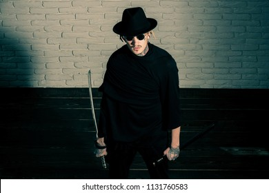 Warrior in black sunglasses, hat and clothes, top view. Man with swords standing on wooden floor. Honor and dignity. Samurai, buddhist concept. Harakiri, suicide ritual.