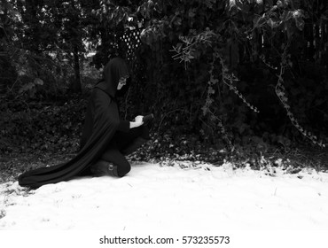 Warrior kneels in snow with sword