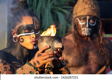 Warrior of Maya stands with goblet of fire on historical festival Times and epochs. Ancient Mayan ritual, show by the Mexican group Xipetotek, reenactors of Maya history - Moscow, Russia, June 2019