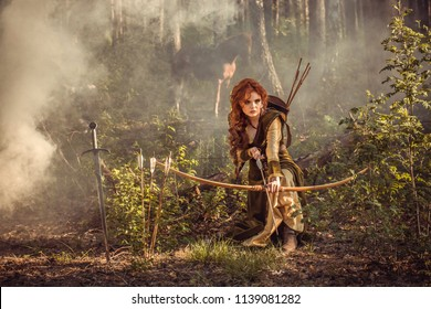 Warrior medieval woman with bow hunting in mystery forest
