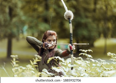 Warrior medieval woman with bow hunting in green forest, close-up